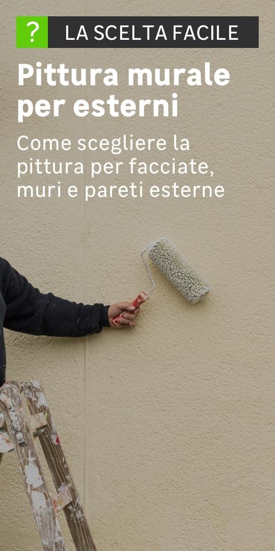 Una persona passa il rullo ricoperto di vernice su una parete esterna